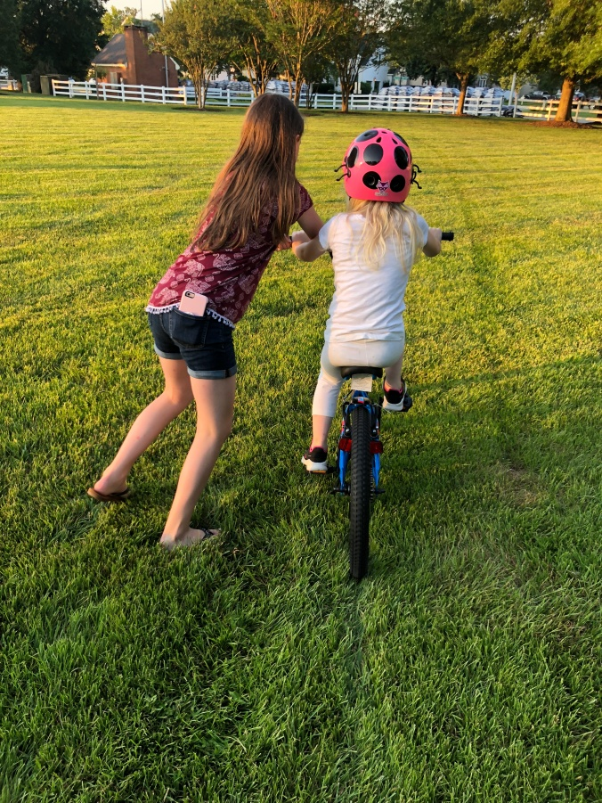 Big sister shows little sister how to ride a big girl bike.